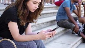 Realtidsskott av kvinnan med smartphonen som sitter på trappan, i Paris att smsa