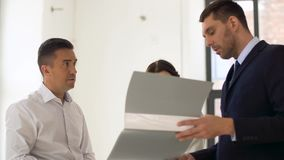 Realtor με το φάκελλο που παρουσιάζει έγγραφα στους πελάτες απόθεμα βίντεο