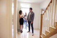 Realtor που παρουσιάζει νέα οικογένεια γύρω από την ιδιοκτησία για την πώληση στοκ εικόνες
