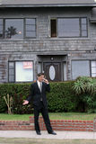 Realtor,business man, Series. A realtor, or business man, or renter or building owner, talks on his cell phone while outside his home with a for rent sign in the Stock Images