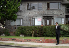 Realtor, business man, Series. A realtor, or business man, or renter or building owner, talks on his cell phone while outside his home with a for rent sign in Stock Photo