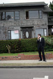 Realtor,business man, Series. A realtor, or business man, or renter or building owner, talks on his cell phone while outside his home with a for rent sign in the Stock Photography