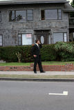 Realtor,business man, Series. A realtor, or business man, or renter or building owner, talks on his cell phone while outside his home with a for rent sign in the Stock Photos