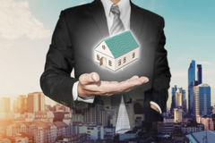 Realtor businessman with home model on hand, with urban city view in sunrise background Stock Photography