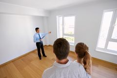 Realtor with clipboard and couple at new home Stock Photography