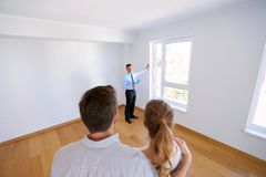Realtor with clipboard and couple at new home Stock Image