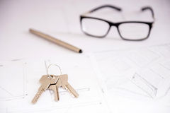 Realtor. Close-up key on the plan of house, financial contract, pen and glasses Royalty Free Stock Image