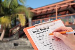 Realtor Completes a Real Estate House Listing. Realtor writes out a real estate listing outside a house for sale Royalty Free Stock Images