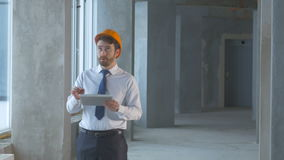 Realtor, construction engineer, businessman inside a new building inspecting construction site using tablet. Construction engineer, businessman inside a new stock video footage