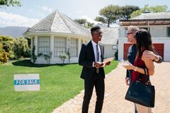 Realtor and couple in front of house for sale. Real estate broker meeting and talking with clients outside a luxury villa. Realtor outside house for sale with a royalty free stock photo