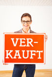 Realtor In Empty Apartment, Holding `verkauft` Sign Royalty Free Stock Image