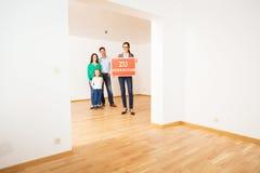 Realtor In Empty Apartment, Holding `zu Verkaufen` Sign Stock Photography