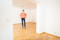 Realtor In Empty Apartment, Holding `zu Verkaufen` Sign Stock Photos