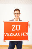 Realtor In Empty Apartment, Holding `zu Verkaufen` Sign Royalty Free Stock Image