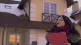 Realtor evaluate a building and territory around it. Beautiful with red lips stands at the background on the house. Realtor evaluate a building and makes some stock video footage