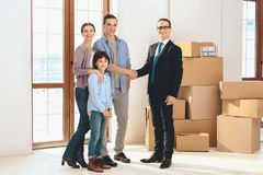 Realtor with family in new apartment with cardboard boxes. Father and realtor are shaking hands. stock photography