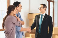 Realtor with family in new apartment with cardboard boxes. Husband and realtor are shaking hands. Realtor in suit with family in new apartment with cardboard stock photography