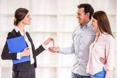 Realtor. Female realtor is giving to young couple a key from new flat stock photo