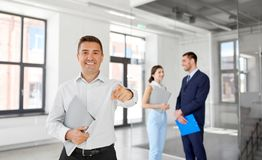Realtor with folder pointing at you at office Royalty Free Stock Image