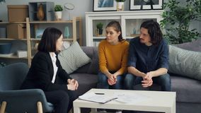 Realtor discussing real estate deed with buyers husband and wife indoor at table. Realtor friendly young woman is discussing real estate deed with buyers husband stock footage