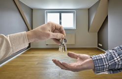Realtor giving house key to buyer. In empty room royalty free stock photo