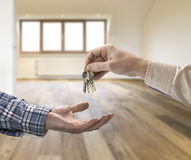 Realtor giving house key to buyer in loft room Stock Images