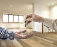 Realtor giving house key to buyer in loft room. Realtor giving house key to buyer in empty loft room royalty free stock photo
