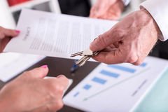 Realtor giving house keys to his client. After signing the contract Stock Photography