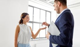 Realtor giving key to customer at new office royalty free stock photo