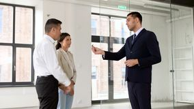 Realtor giving key to customers at new office. Real estate business, sale and people concept - realtor giving key to customers or new office owners stock footage