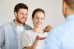 Realtor giving keys from new home to happy couple Stock Photos