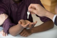 Realtor giving keys to black husband buying home with girlfriend Royalty Free Stock Photo