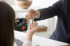 Realtor giving keys to new home female buyer. Close up of realtor giving keys to new house to female buyer purchasing first home, broker making deal with royalty free stock image