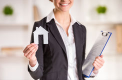 Realtor. Happy realtor woman is holding model of home and smiling Stock Image