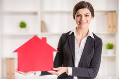 Realtor. Happy realtor woman is showing home for sale sign Stock Images