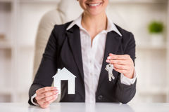 Realtor. Happy realtor woman is showing home for sale sign and keys stock image