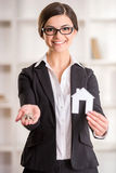 Realtor. Happy realtor woman is showing home for sale sign and keys Royalty Free Stock Photo