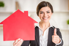 Realtor. Happy realtor woman is showing home for sale sign and thumbs up Royalty Free Stock Photo