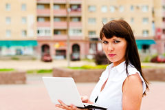 Realtor home. Realtor is a woman with a netbook on the background of the house Royalty Free Stock Photos
