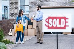 realtor making deal with single mother with sold signboard blurred Stock Images
