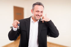 Realtor man is holding house keys. And doing call gesture with hand stock photos