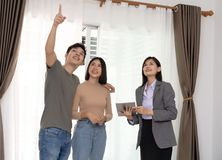 Realtor offer the house and showing young Asian couple with real stock photos