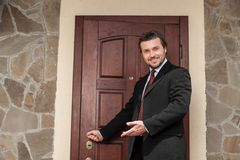 Realtor opening wooden door and smiling welcoming. Royalty Free Stock Image