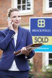 Female Realtor On Phone Outside Residential Property For Sale Royalty Free Stock Image