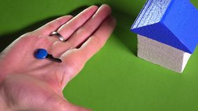 Realtor placing toy house with blue roof and holding small key against green background. Real estate market concept. 4K. Female realtor placing toy house with stock footage