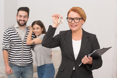 Realtor is playing with keys from new apartment rented by happy young couple. Royalty Free Stock Photo