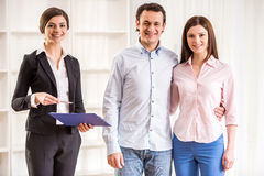 Realtor. Portrait of happy young couple and female realtor in a new flat Stock Photos