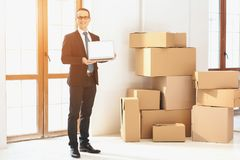 Realtor presenting laptop in new apartment with cardboard boxes near doors. royalty free stock image