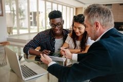 Realtor presenting technical documentation to owner couple. Male real estate agent offering to buy a new house to young couple during a meeting. Realtor Royalty Free Stock Photo