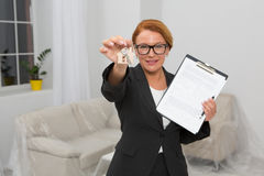 Realtor proposing to sign an agreement for apartment rent, camera focused on hand keeping keys. Royalty Free Stock Photography